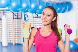 jeune fille buvant une boisson isotonique, salle de gym. Émotions positives. photo