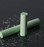 craie cassée verte sur tableau noir avec de la poussière de craie photo