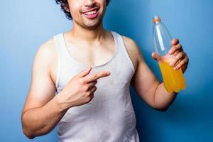 Jeune homme buvant une boisson énergisante après un entraînement en sueur photo