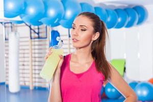 jeune fille buvant une boisson isotonique, salle de gym. elle est heureuse. photo
