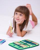petite fille dessine à l'aide de crayons photo