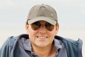 homme en casquette de baseball et lunettes de soleil photo