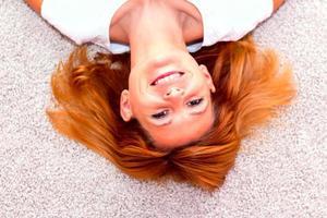 portrait d'une jeune femme rousse souriante.