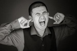 modèle isolé sur fond uni boucher les oreilles avec les doigts photo