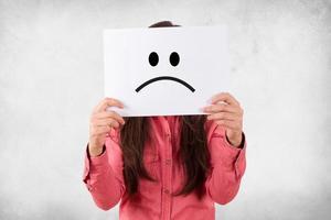 femme tenant une carte blanche avec une expression triste