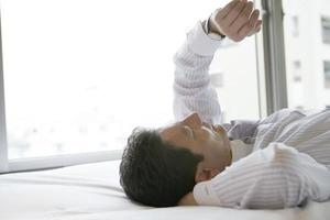 homme affaires, coucher lit, regarder montre