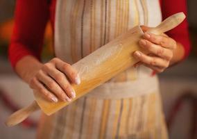 Gros plan sur la jeune femme au foyer tenant un rouleau à pâtisserie