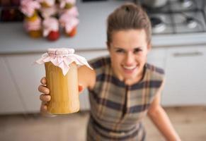 Gros plan sur une femme au foyer heureuse montrant un pot avec de la confiture de pommes maison