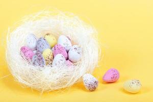 oeufs de pâques dans un nid blanc photo
