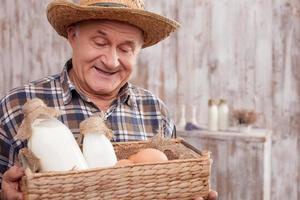 joyeux vieux travailleur masculin avec des produits laitiers photo