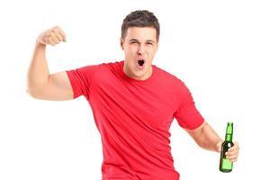 fan euphorique tenant une bouteille de bière et applaudir photo