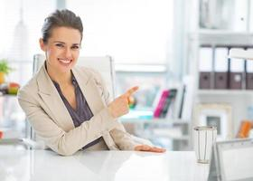femme d'affaires heureux au bureau pointant sur l'espace de copie photo