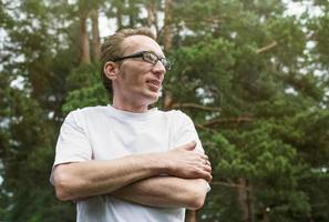 homme heureux en plein air avec les bras croisés. copier l'espace à droite. photo