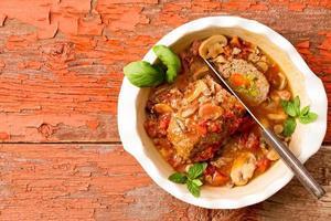 Pain de viande en tranches dans une casserole sur une table rustique avec espace copie