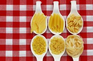 Pâtes alimentaires non cuites sur des cuillères sur un tissu à carreaux avec copie espace photo