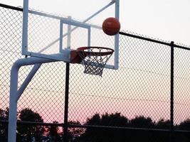 panier de basket avec une balle au coucher du soleil. photo