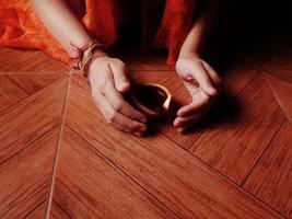 mains humaines illuminant la lampe à huile. photo
