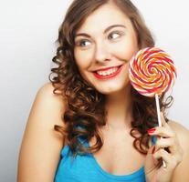 drôle femme bouclée tenant grosse sucette. photo
