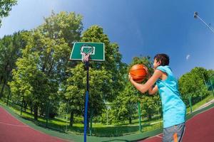 garçon arabe tient la balle pour lancer dans le but de basket-ball photo