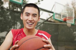 jeune homme assis avec un ballon de basket, portrait photo