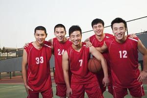 équipe de basket-ball debout et souriant, portrait photo