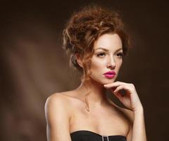 fille de mannequin de beauté aux cheveux roux bouclés, longs cils. photo