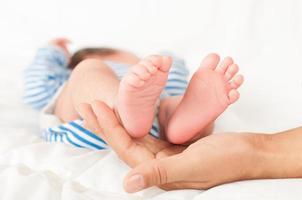 les mains de la mère tiennent les jambes du bébé