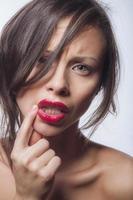 les femmes redresse le rouge à lèvres de son doigt photo