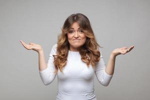 haussant les femmes dans le doute faisant hausser les épaules photo