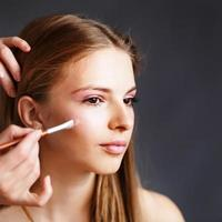 jeune fille blonde appliquant le maquillage par maquilleuse. photo