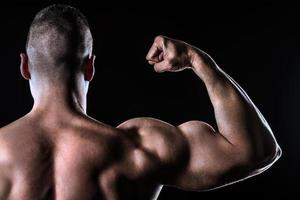 athlète fort montrant vue arrière biceps isolé sur noir photo