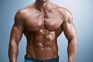 constructeur de corps masculin attrayant sur fond bleu photo