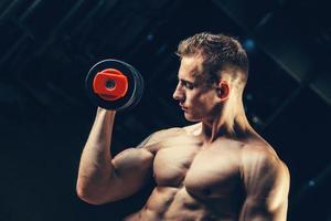 Bodybuilder musculaire athlète retour avec haltère dans la salle de gym photo