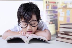 élève de maternelle lit des manuels photo