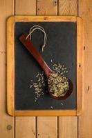 mélange de riz dans une cuillère en bois sur un tableau noir photo