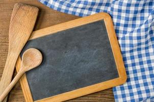 tableau noir avec des cuillères en bois sur une nappe à carreaux bleu