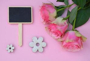 fond rose et roses, avec étiquette de tableau de craie noire vide photo