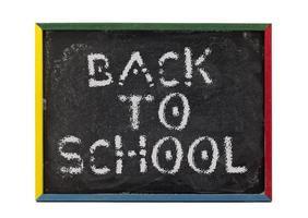 retour à l'école écrit sur le tableau noir des petits étudiants photo
