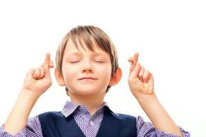 écolier mignon en gardant les doigts croisés photo