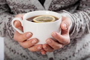 mains tenant une tasse de thé photo