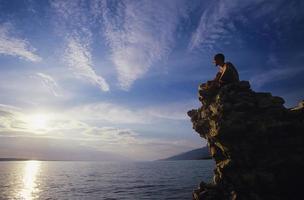 homme assis sur un rocher surplombant l'océan photo