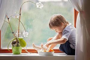 mignon petit garçon, assis sur la fenêtre, manger des fruits
