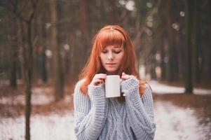 photo fille rousse avec une tasse à la main.