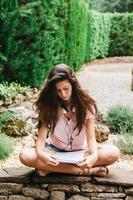 belle jeune femme assise à l'extérieur et étudier. photo