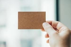 main tenant la carte de visite d'artisanat sur l'arrière-plan flou photo