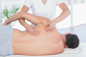 physiothérapeute faisant massage du dos à son patient photo