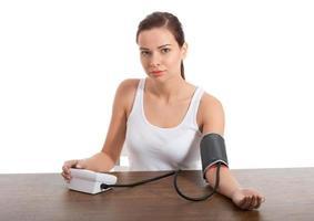 belle jeune femme prenant le test de pression artérielle. photo