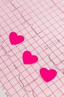 coeurs de papier sur le graphique de l'électrocardiogramme, la médecine et le concept de soins de santé photo