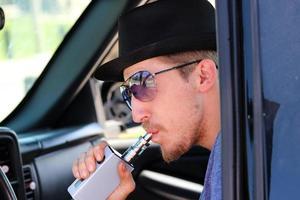 homme inhale à l'aide d'un dispositif de vapotage électronique photo