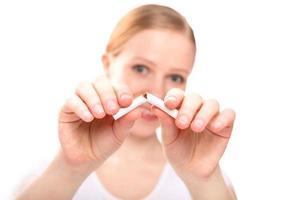 femme brisant la cigarette. concept arrêter de fumer photo